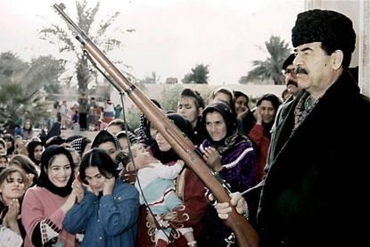 http://worldmeets.us/images/Saddam-Hussein-gun-hat_pic.png